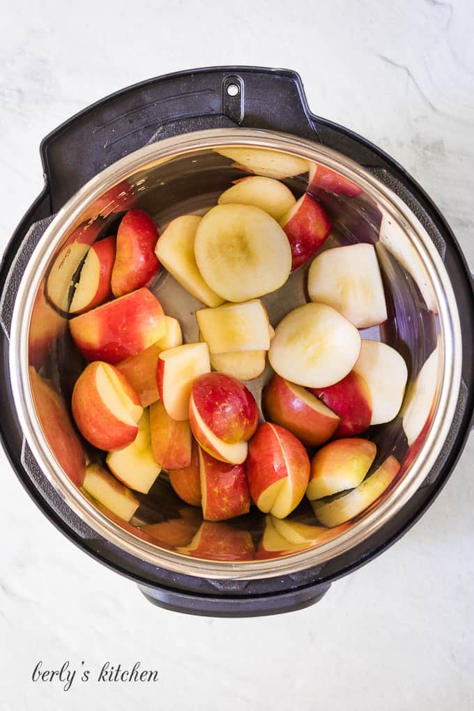 Apples have been tossed with lemon juice in the cooker.