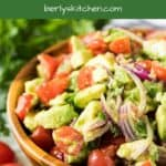 The tomato avocado salad served in a decorative wooden bowl.