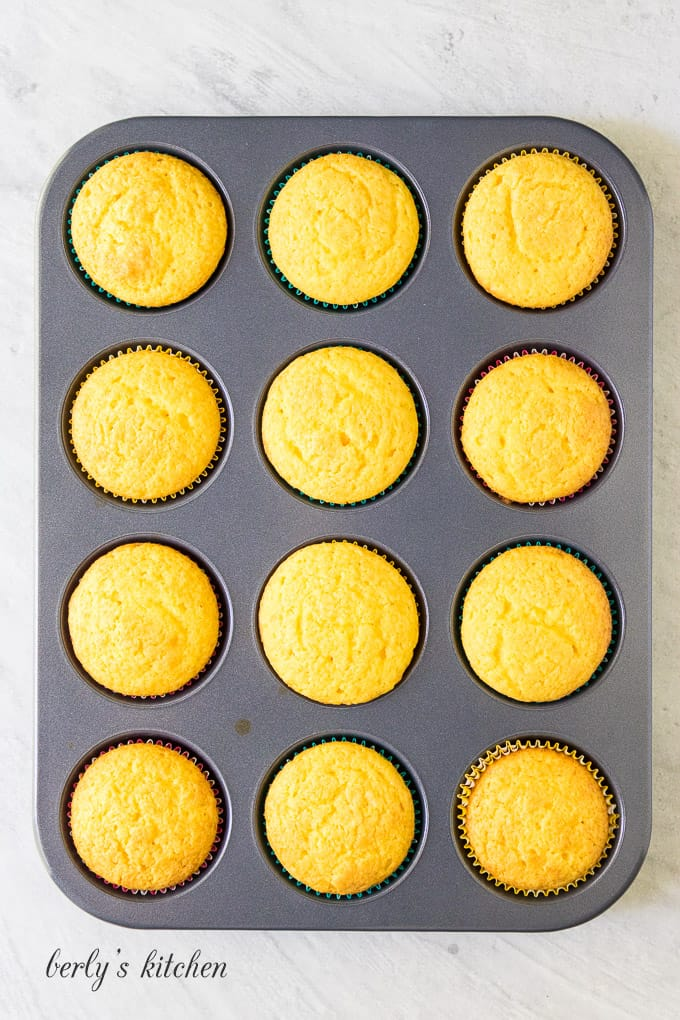 The cupcakes have baked and are cooling before being frosted.