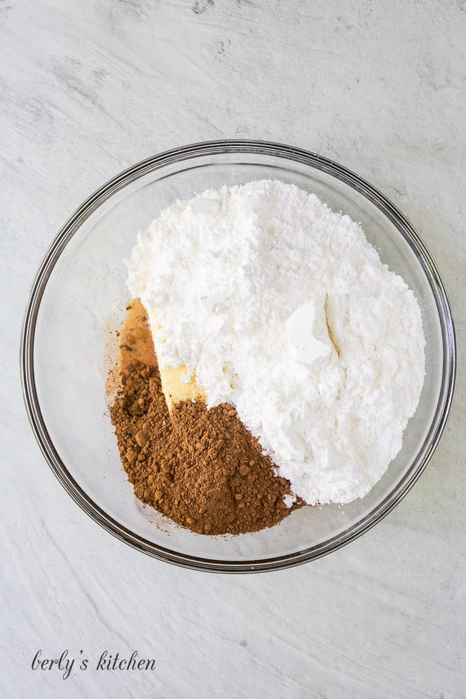 The sugar, butter, and other frosting ingredients in a bowl.