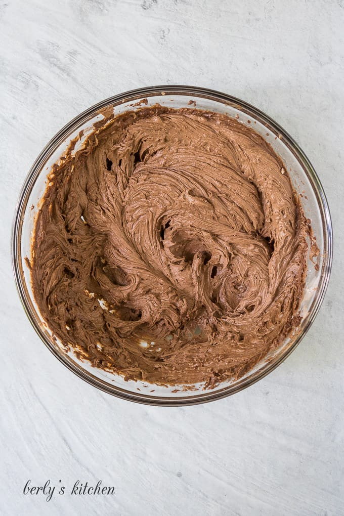 The chocolate buttercream frosting has been mixed in a glass mixing bowl.
