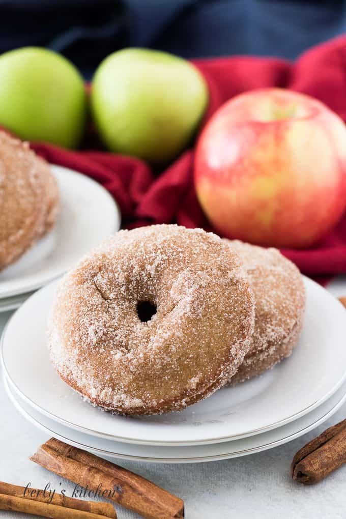 Two finished apple donuts sitting on a small white plate.