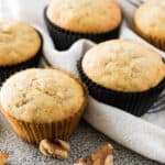 Five banana muffins on a white towel surrounded by walnuts.