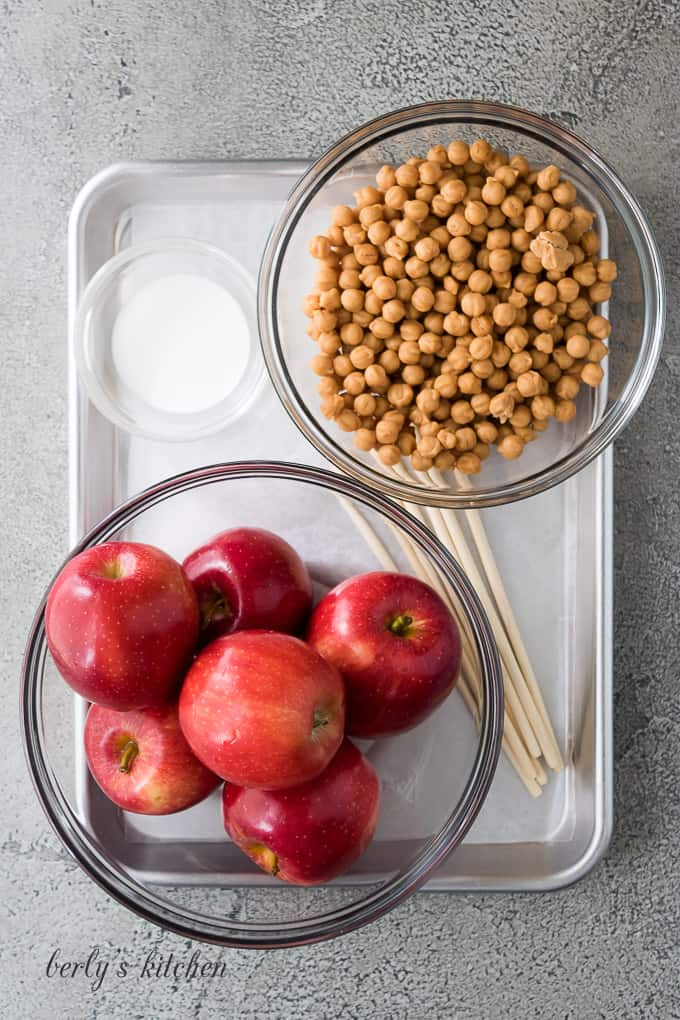 Apples, heavy cream, and other ingredients on a sheet pan.