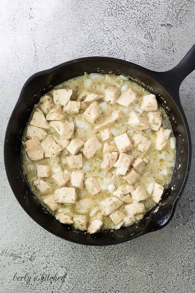 Butter, meat, and seasonings cooking in a cast iron skillet.