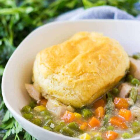 Chicken pot pie topped with a biscuit in a bowl.