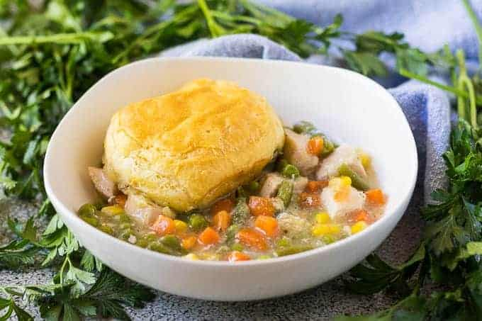 A scoop chicken pot pie served in a white bowl.