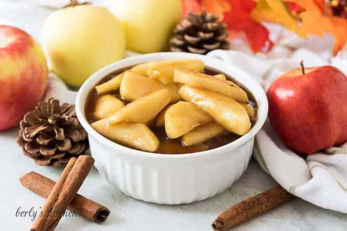 A bowl of the cinnamon apples accented with cinnamon sticks.