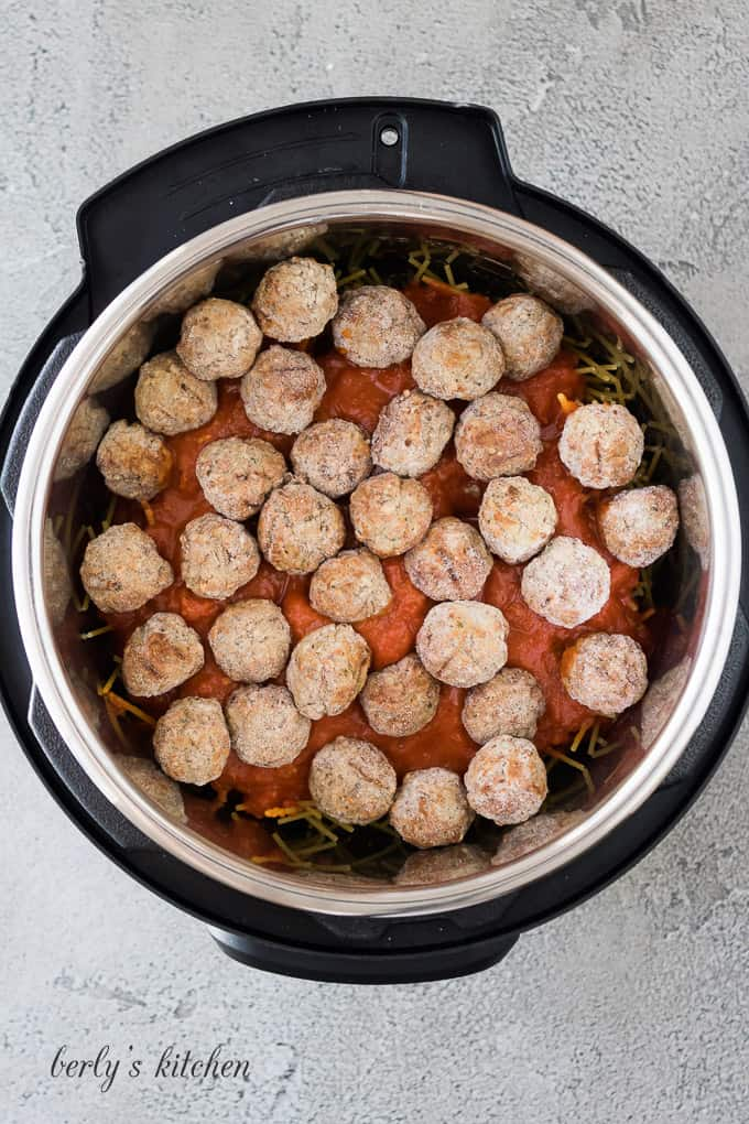 Pasta sauce and meatballs have been added to the noodles.