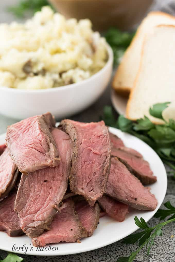 Mashed potatoes, bread, and sliced beef in separate white dishes.
