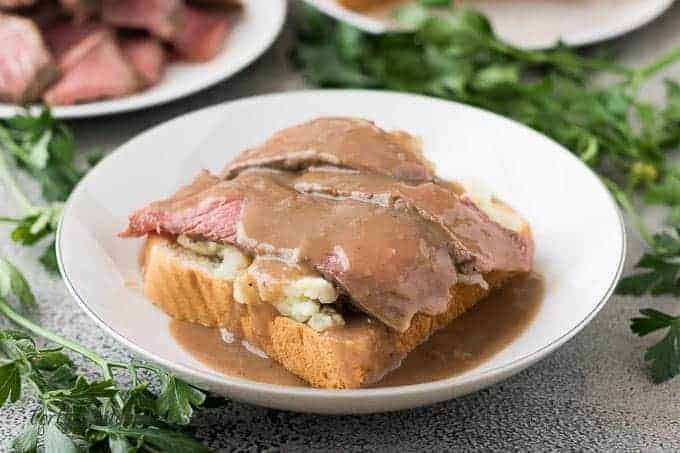 Leftover pot roast atop mashed potatoes and bread topped with gravy.