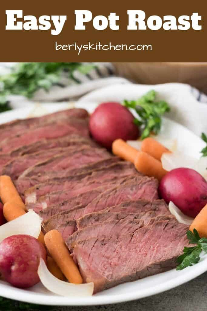 Sliced beef pot roast surrounded by carrots, onions, and potatoes.