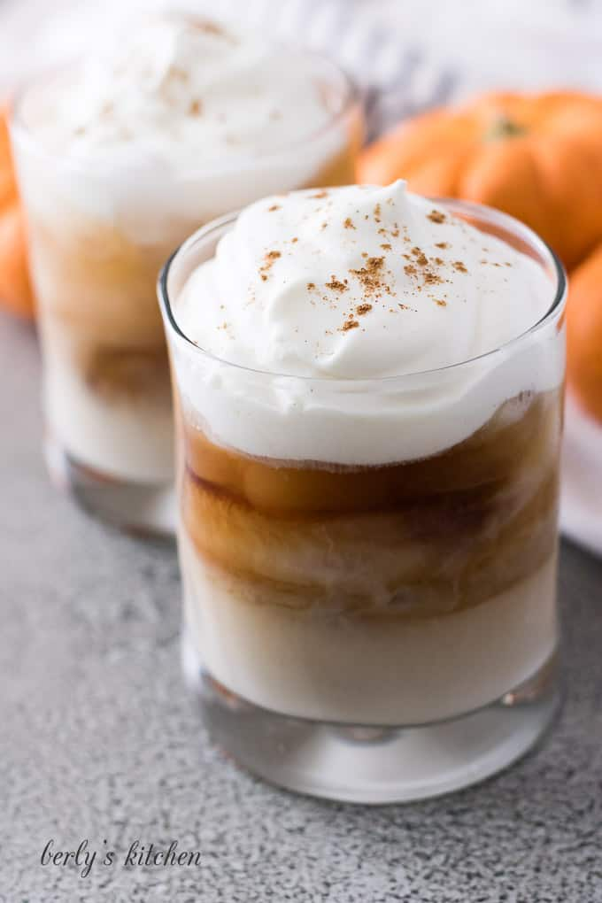 Two cocktails garnished with whipped cream and pumpkin pie spice.