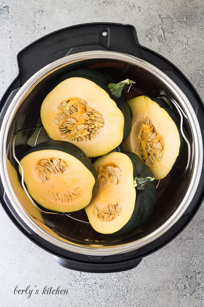 The acorn squash has been added to the cooker liner.
