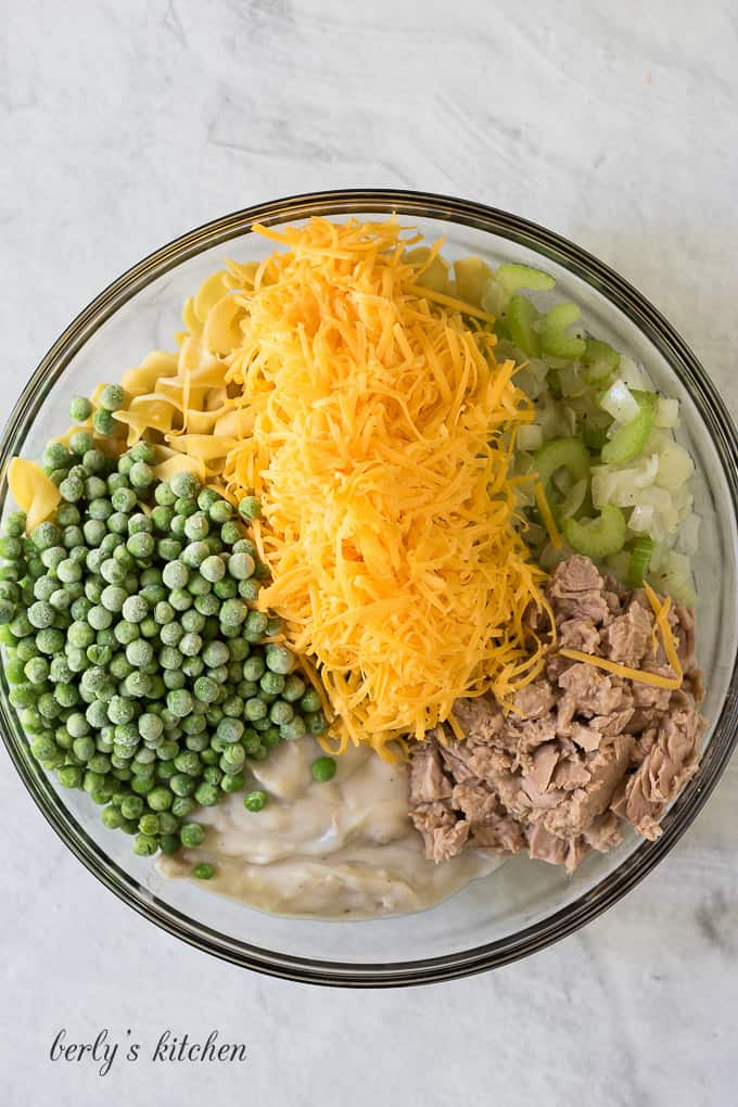 A mixing filled with cheese, peas, and other casserole ingredients.