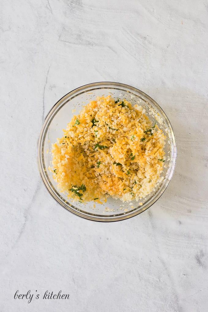 The breadcrumbs and seasonings mixed in a small glass ramekin.