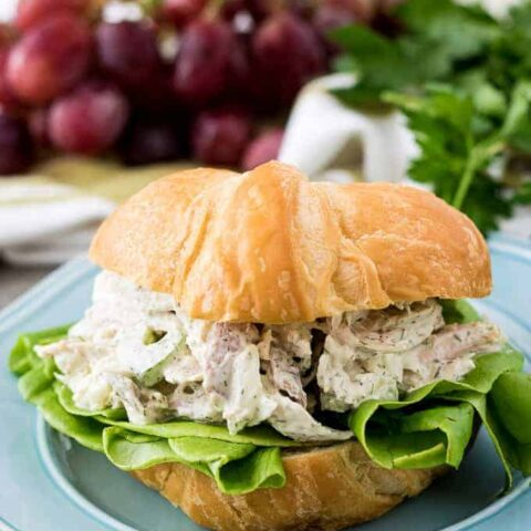 A turkey salad sandwich with lettuce on a golden croissant.