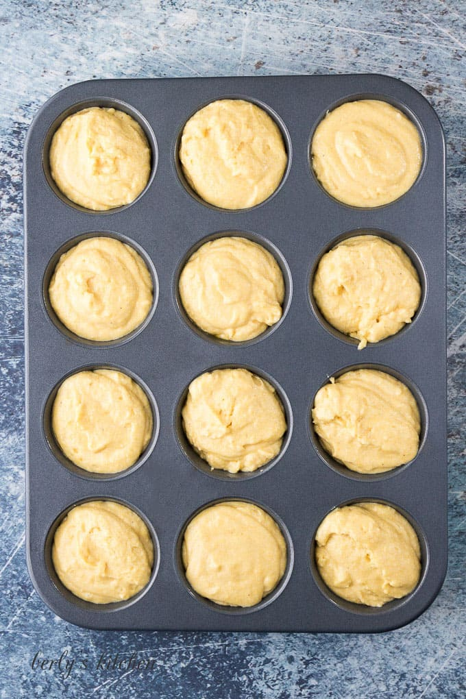 A large muffin tin filled with the cornbread muffin batter.