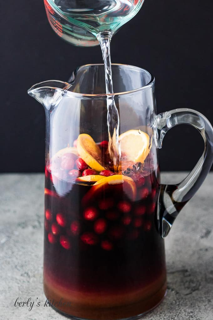 Club soda being poured into the pitcher filled with fruit and brandy.
