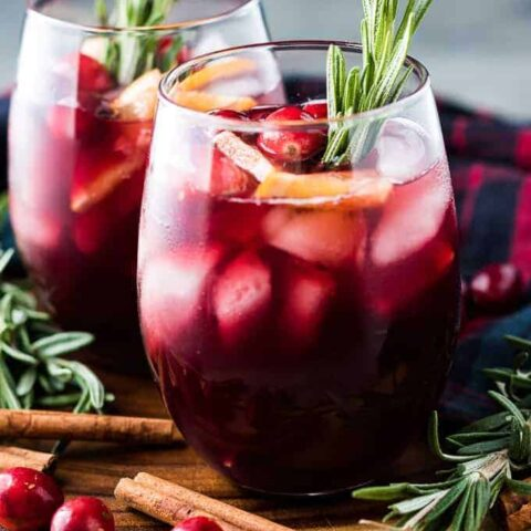 Two glasses of sangria garnished with cranberries and orange slices.