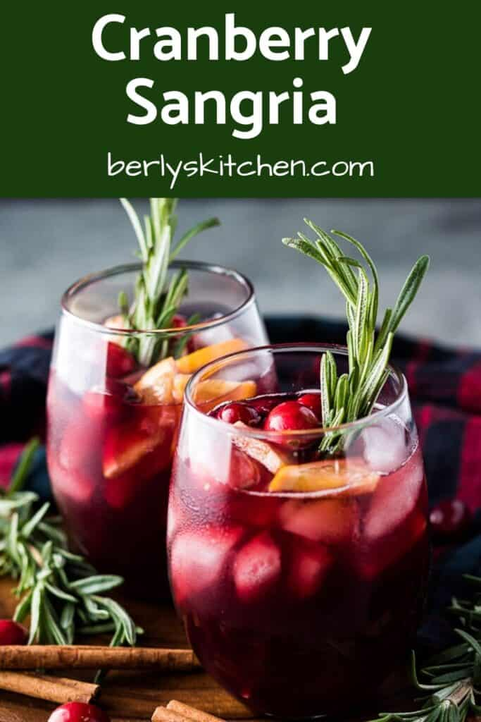 Two glasses of cranberry sangria garnished with cranberries and oranges.