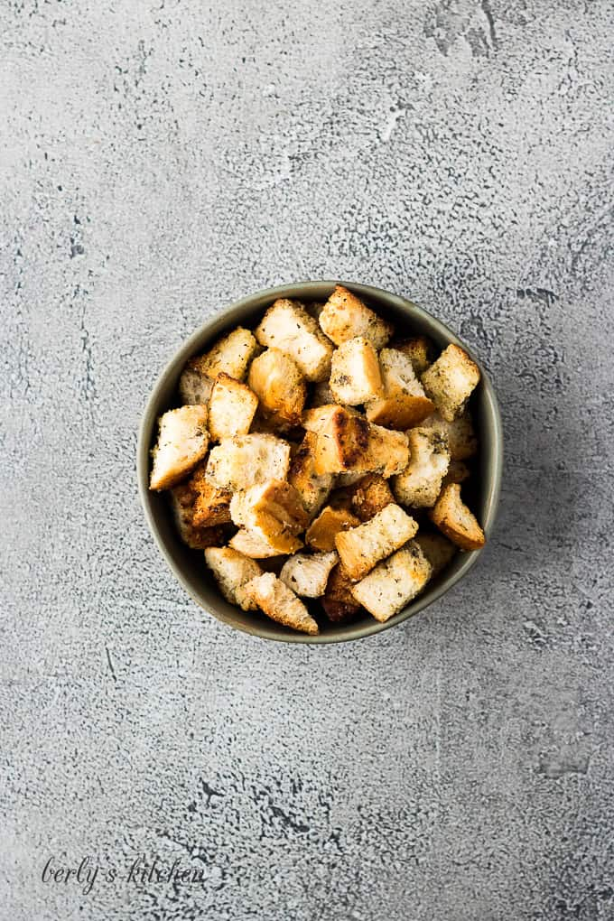 An aerial view of the finished buttery croutons in a bowl.