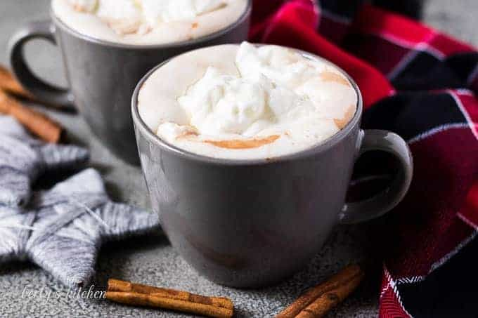 Two mugs of gingerbread hot chocolate topped with whipped cream.