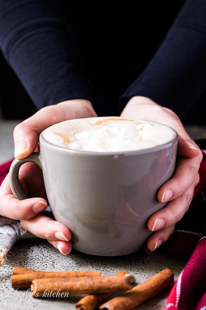 Hand model holding a mug of the gingerbread hot chocolate.