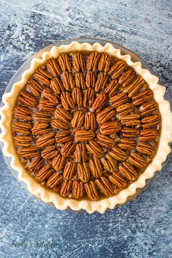 Raw pecans have placed on top the pie for decoration.