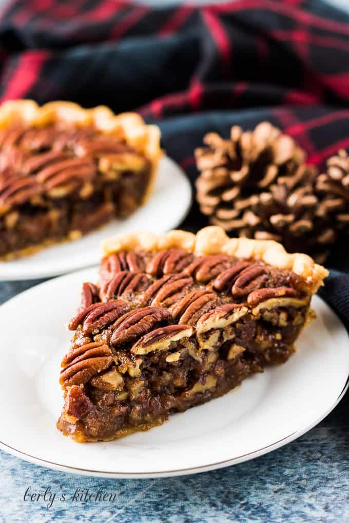 Two slices of pecan pie served on small decorative saucers.