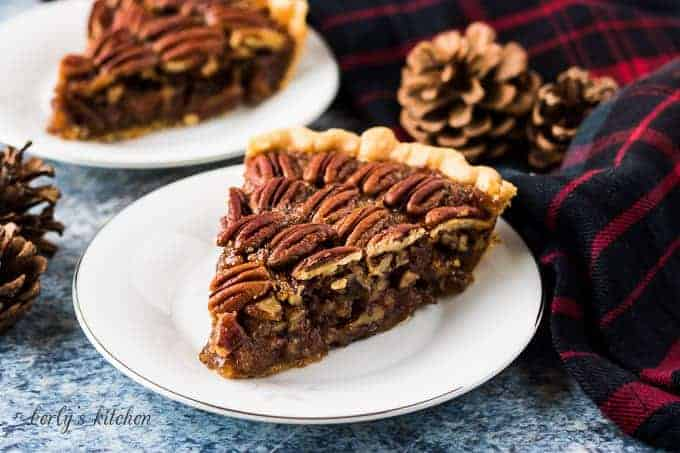 A slice of pecan pie on a small decorative saucer.