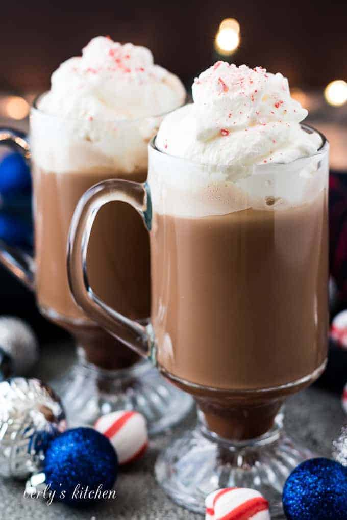 The finished coffees in glass mugs garnished with whipped cream.