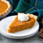 A slice of the sweet potato pie topped with whipped cream.