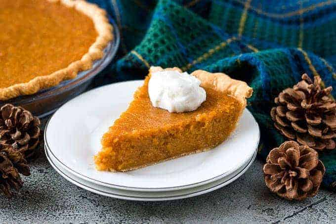 A slice of sweet potato pie topped with whipped cream.