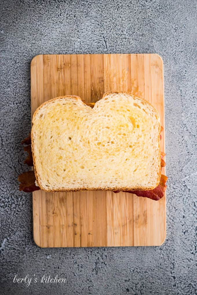 A buttered slice of sourdough atop the bacon and cheeses.