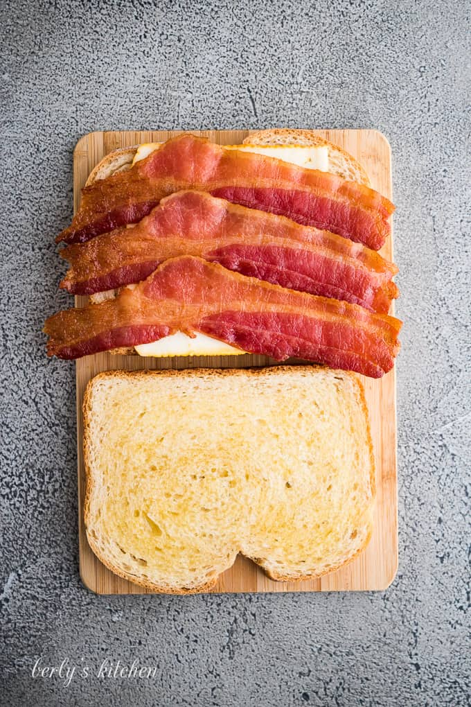 A slice of buttered sourdough with cheese and cooked bacon.