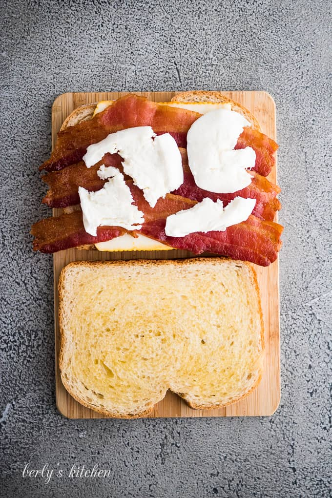 Sliced mozzarella cheese has been placed atop the cooked bacon.