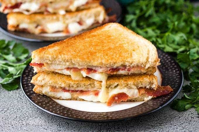 The bacon grilled cheese sandwich halved to show melting cheese.