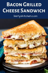 Two bacon grilled cheese sandwiches stacked on a decorative plate.