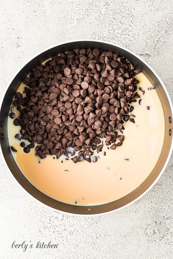 Chocolate chips and other ingredients melting in a large pan.