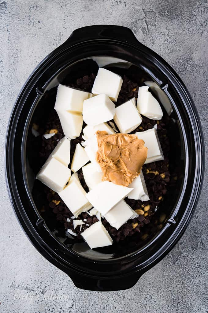 Almond bark, peanuts, and other ingredients layered into a crockpot.