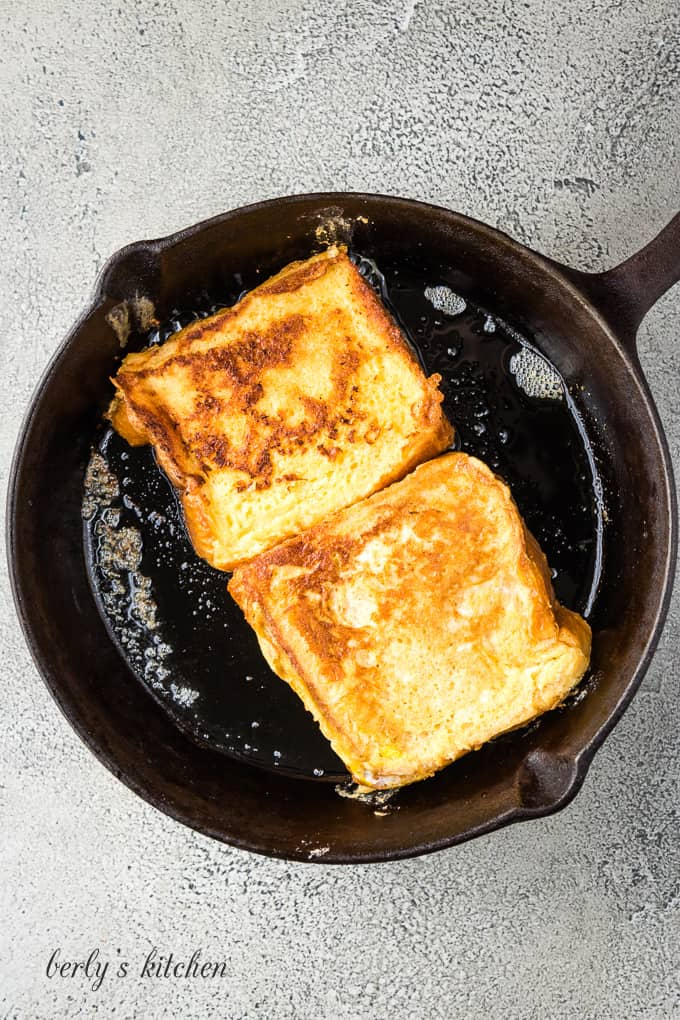 Two pieces of toast being cooked in an iron skillet.