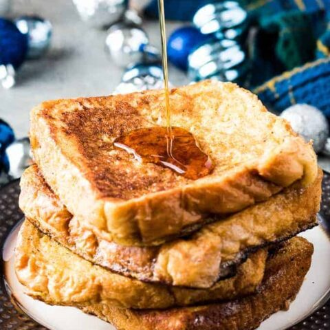 A stack of French toast being drizzled with maple syrup.