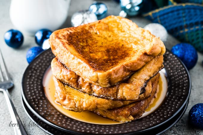 Four pieces of eggnog French toast drizzled with maple syrup.