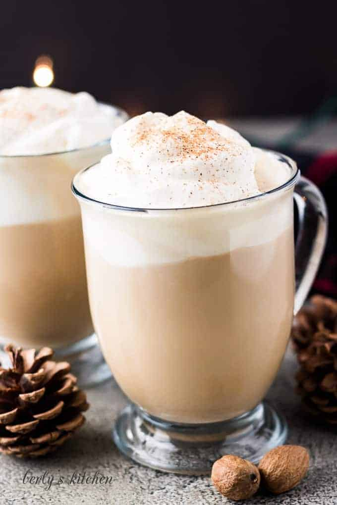 Two finished eggnog latte coffee drinks served with whipped cream.