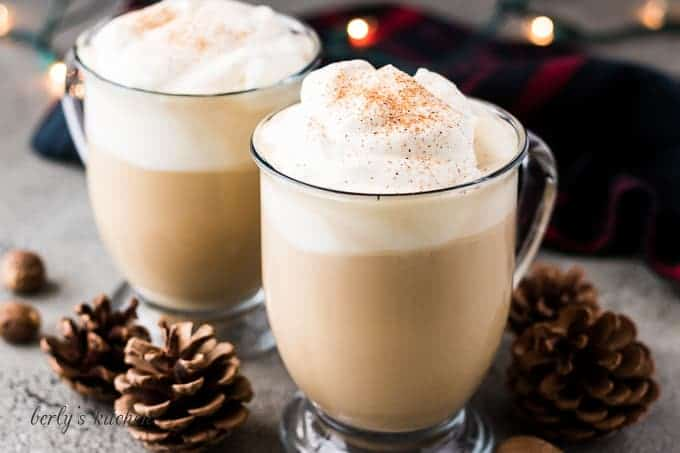 Two eggnog lattes served in clear mugs with whipped cream.