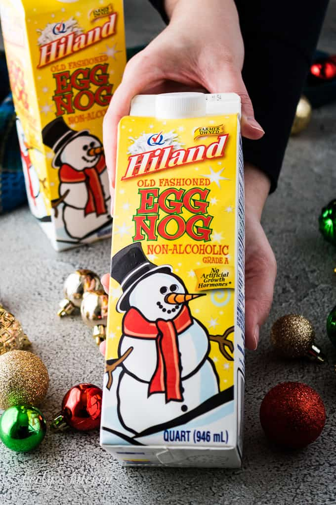 Kim holding an unopened carton of Hiland Dairy brand eggnog.