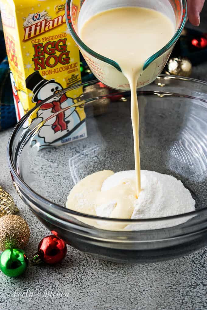 Eggnog being poured into a bowl with instant pudding mix.