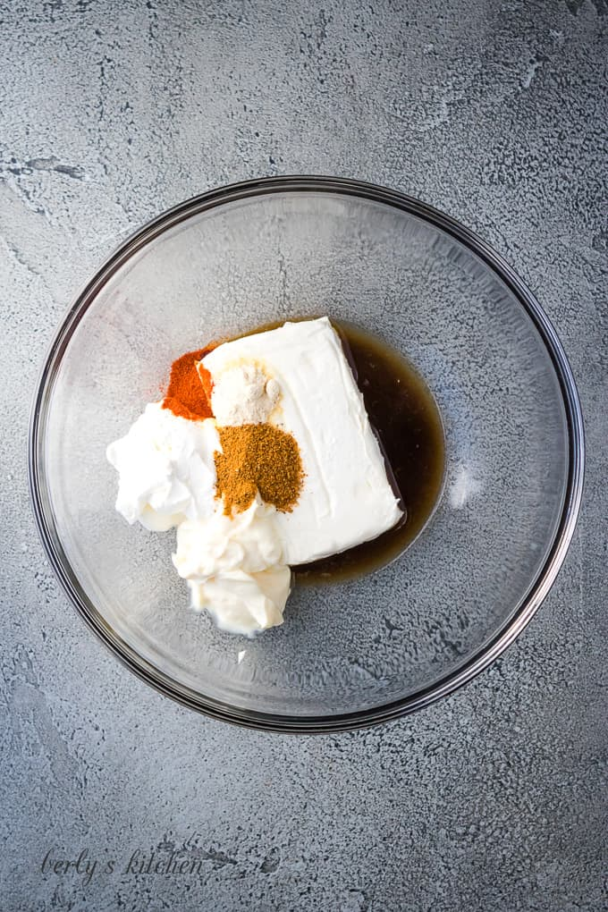 Cream cheese, spices, and other ingredients in a mixing bowl.