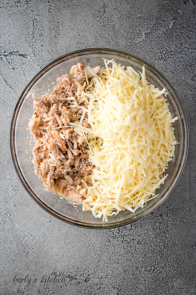 Cheddar cheese and crab have been added to the bowl.